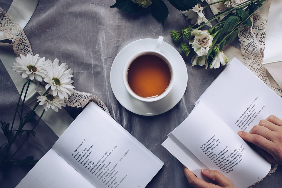 cup of tea on a table with books and flowers