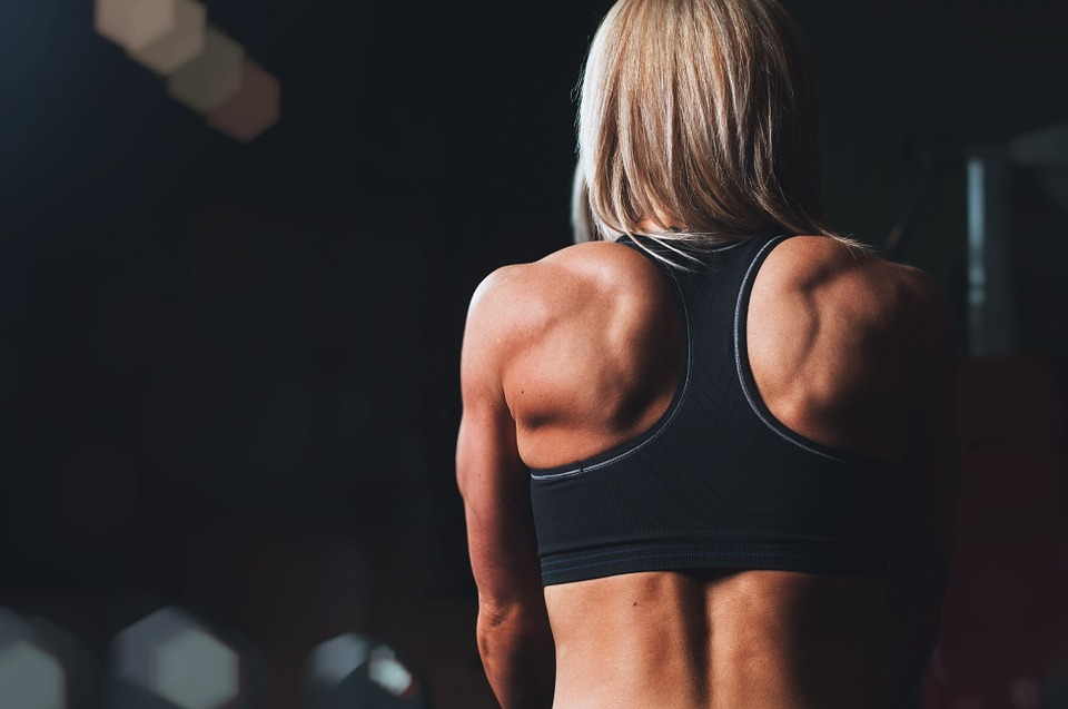 looking good at the gym: blond woman in black gym top, back to viewer.