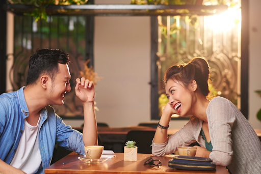 Asian dating sites Asian couple sitting across from each other at a table and laughing