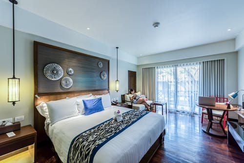 Make your bedroom: large bedroom with dark wood flooring and blue and white bedding.