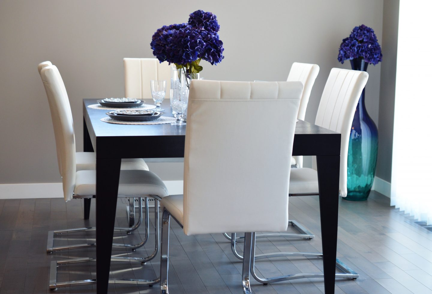 your dining room: black table set, with purple flowers and 6 white chic chairs.