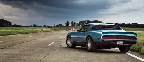 car safety: Blue Coupe on open road with dark clouds in the distance.