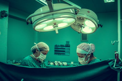 hospital stay: 2 doctors in scrubs performing surgery.