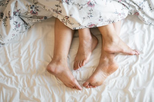 UTI's after having sex: couple with feet protruding from bottom of duvet.