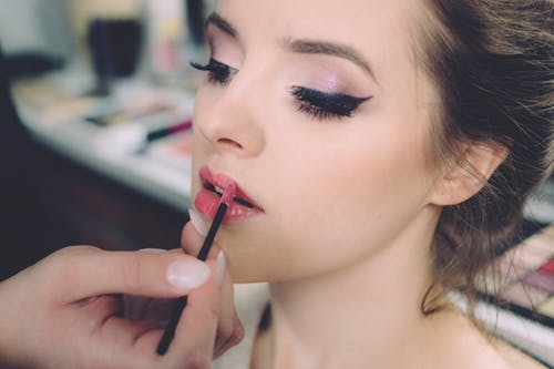 skin treatments: young lady with smooth skin putting on lipstick.