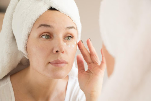A woman with green eyes with hair wrapped in a towel looking in the mirror and applying a cream under her eyes
