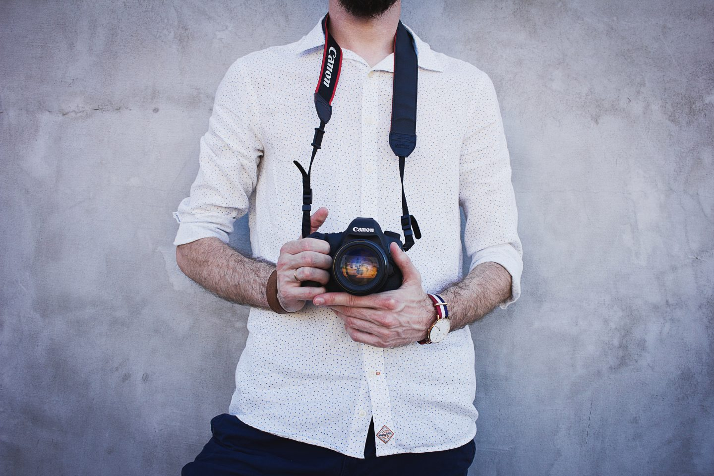 Photographer holding his camera: hire a professional wedding photographer
