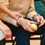 memory care home: young person holding the hand of an elderly man.