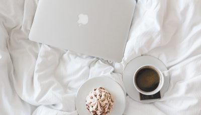 a closed laptop a coffee cup and pastry on a bed