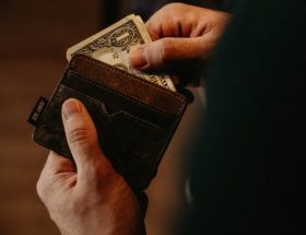 fast finances: person taking cash out of brown wallet.