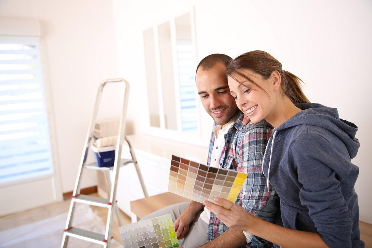 home renovation worries: couple looking at paint brochure while taking a break from painting a room.