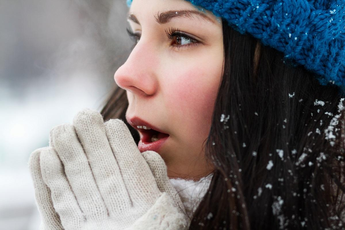 woman blowing on her hands to warm up during a snowy day