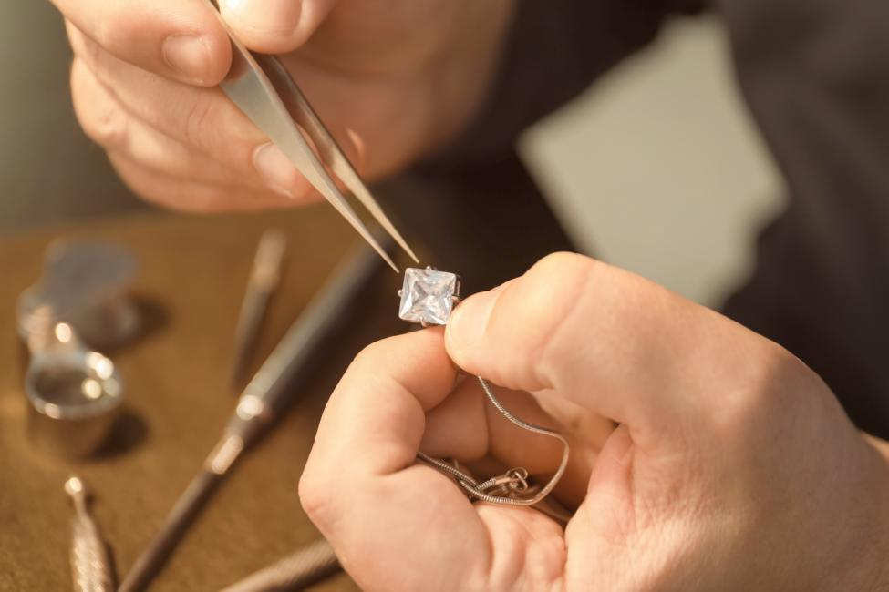 outdated jewelry: jeweler repairing a diamond necklace.
