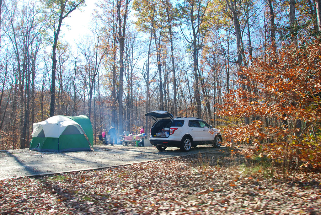 Road Trip Budget: SUV car with boot open in woods with camping tent and family cooking a BBQ beside it.