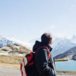 backpacking: man with backpack looking up at snow covered mountains by a lake.