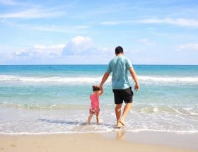 take more holidays next year: man and small boy walking on seashore on a sunny day.