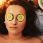 tightening your skin: woman with cucumber slices on her eyes.