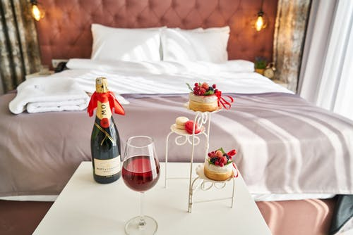 wine bottle and food on hptel room table in frontt of double bed: which hotel rating.