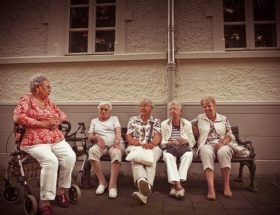 difficult old age: 5 women sitting on a bench and one in a mobility chair outdoors.