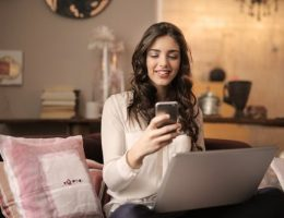 UK's leading marketplace provider: woman on sofa looking at laptop and holding mobile phone.