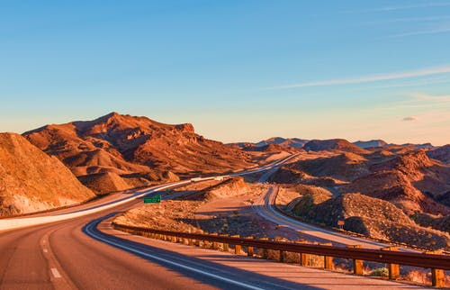 road trip: winding dry mountain road.