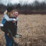 excitement to your relationship; couple ina brown field laughing.