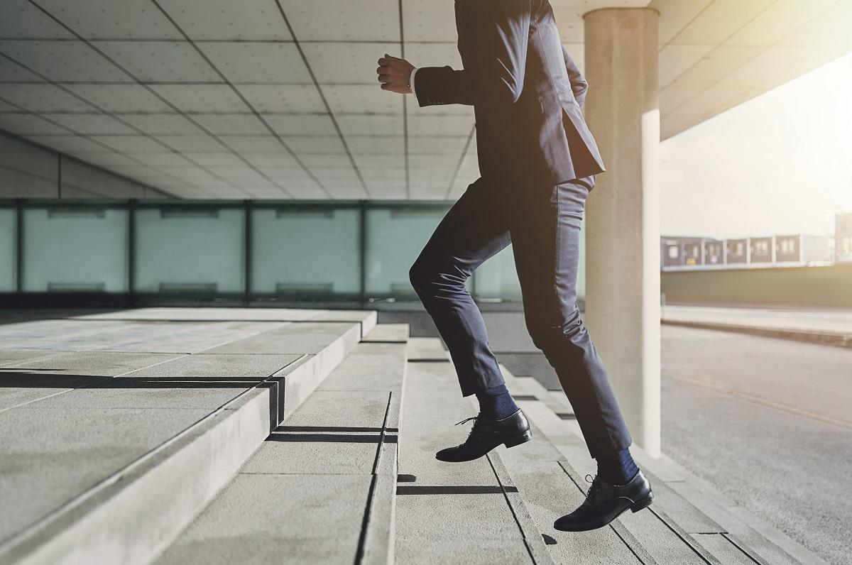what do employers think of tattoos?: man running up stairs wearing suit.