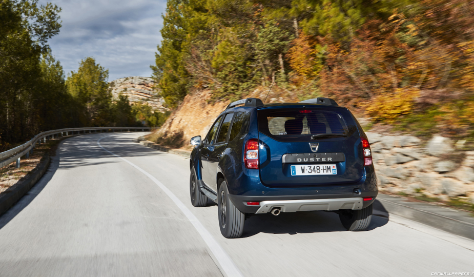 save money on spare parts: Blue Dacia Duster on sunny open road in countryside