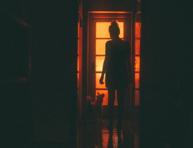 elements of confidence: lady standing in soft light by doorway.