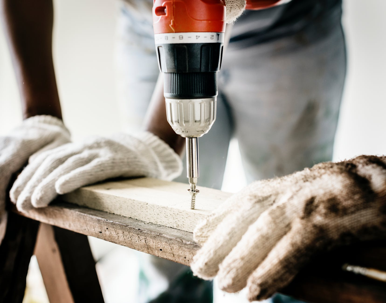 home improvement: man drilling into wooden plank.