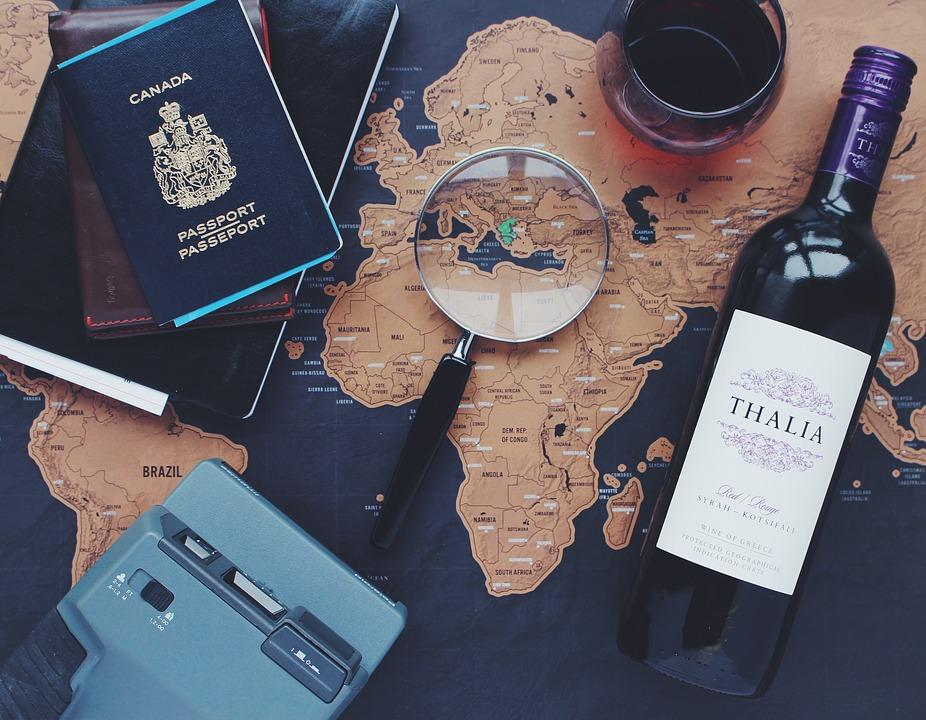 flatlay of world map with passport, wine bottle, and magnifying glass