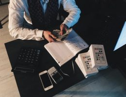 big expenses: man sitting at desk sorting out cash.