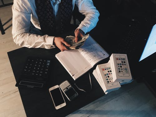 big expenses: man sitting at desk sorting out cash.
