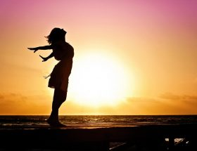 Personal Pulse Oximeter: woman stretching with setting sun behind her.