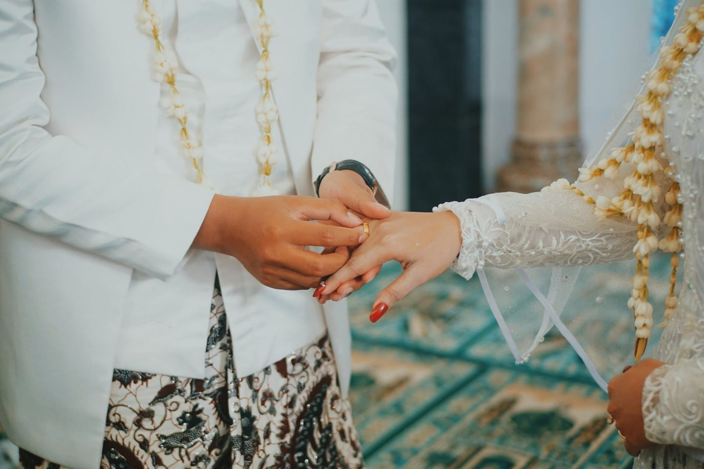 Indian groom putting a ring on his bride's finger