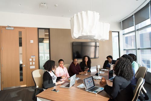 education and training: group of people sitting talking at a large wooden desk.