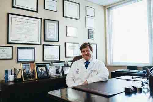 older people: doctor sitting at a desk.