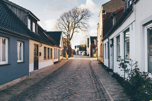 rows of houses on either side of cobbled street: buying my first house.