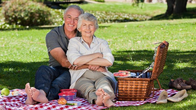 older couple hugging and having a picnic in park