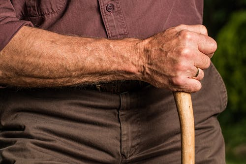 older people: man holding wooden cane.