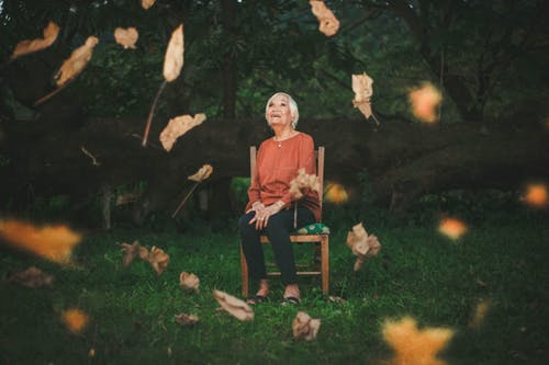 older people: older lady sitting in garden looking up at falling leaves and smiling.