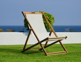 white beach chair on artificial grass with the sea in background