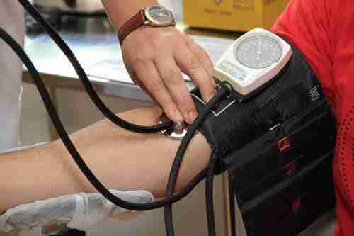 heart check ups: person having blood pressure taken.