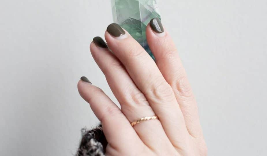 gemstones and gold: person holding up a green gemstone.