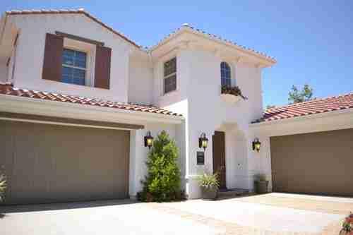 garage door repair: large house with brown garage door.