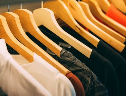 our wardrobes: collection of tops on hangers.