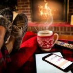 Warm up your home: person sitting at sofa with a hot drink in front of a fire.