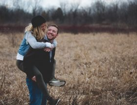 man carrying woman piggy back in field: cuffing season
