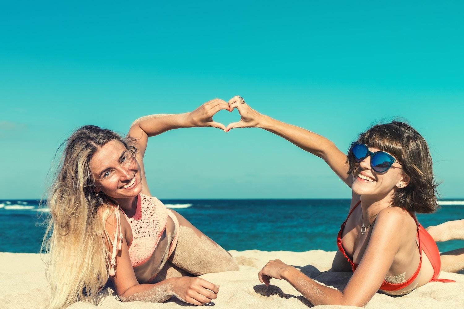 your trip to Florida: 2 women sun bathing and smiling on beach