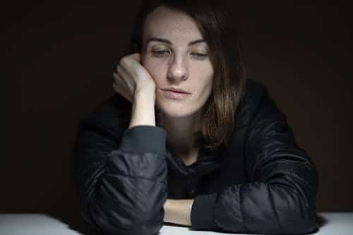 Woman holding face and looking sad: consider psychotherapy